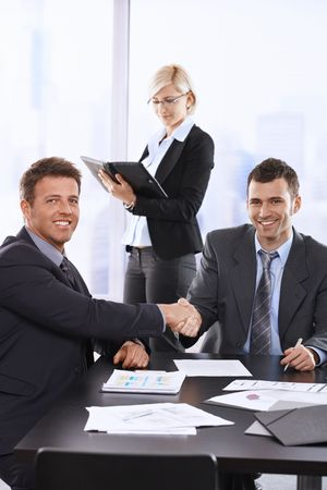 Businessmen shaking hands at meeting, sitting at table, assistant in background holding organiser. Stock Photo - 6527294