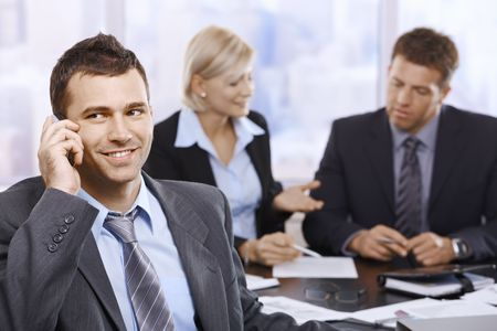 Businessman talking on mobilephone smiling looking aside at meeting. photo