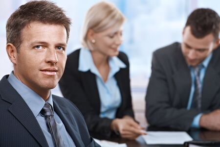 Portrait of businessman looking at camera sitting at meeting room with coworkers. Stock Photo - 6527275