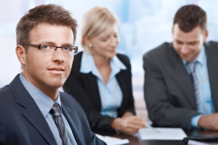 Portrait of businessman looking at camera sitting at meeting room with partners. Stock Photo - 6527333