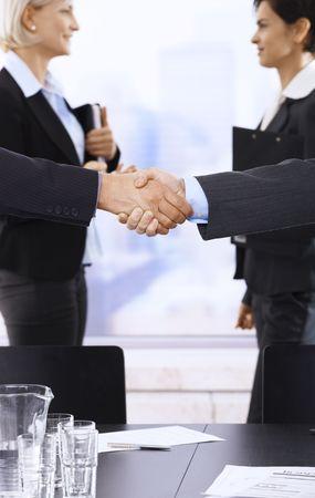 Closeup handshake in focus, businesswomen smiling in background in meeting room. photo