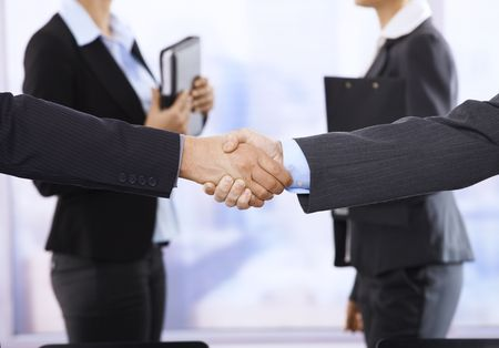 Closeup handshake in focus, businesswomen in background in meeting room. Stock Photo - 6544360