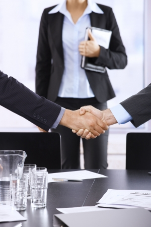 three persons: Businessmen shaking hands in office, assistant in background, handshake in closeup.