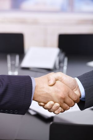 Closeup of hands. Businessmen shaking hands over table, in office meeting room. Stock Photo - 6544386