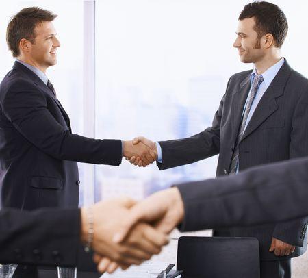 Handshake in closeup, smiling businessmen shaking hands in background of skyscraper office. photo