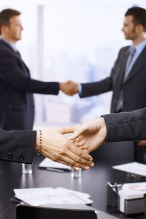 Businesspeople shaking hands in skyscraper office on meeting. Focus on hands. Stock Photo - 6527148