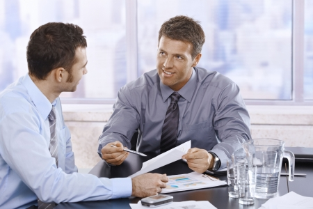 işadamları: Happy businessmen discussing business report sitting at meeting table in office.