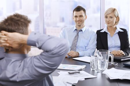 Professionals sitting at at meeting table in skyscraper office, smiling, looking at executive. photo