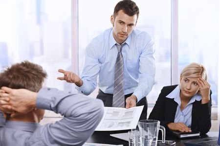 employment issues: Troubled businesspeople discussing report at meeting, businessman showing document to boss with asking gesture. Stock Photo