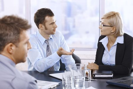 listening to people: Businessman talking to businesswoman at business meeting in office. Stock Photo