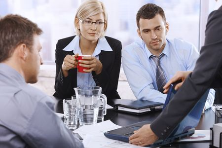 seminar room: Business team at discussion, looking at laptop, businesswoman drinking coffee looking at screen.