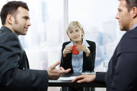 Businesswoman drinking coffee, looking at colleagues discussion at office table. photo