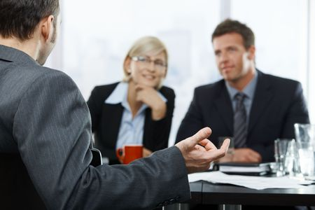 businessmeeting: Focus placed on hand gesturing to colleagues in the background at businessmeeting. Stock Photo