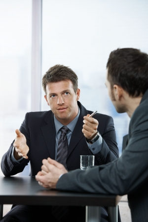 two people talking: Two businessmen discussing tasks sitting at office table.
