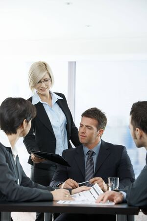 Assistant handing report to executive at meeting in office. photo