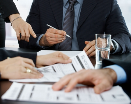 reviews: Hands in closeup at businessmeeting focusing on business documents and pointing at papers to sign.