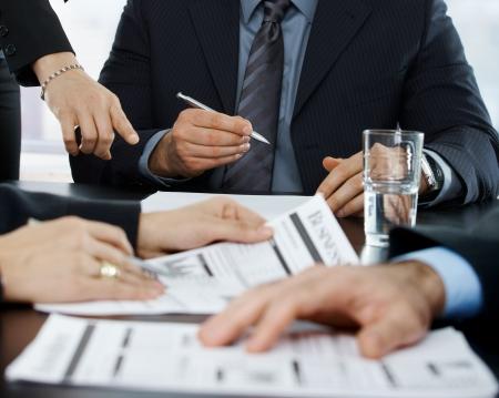 signing: Mani in alzato a businessmeeting concentrandosi su documenti aziendali e che punta a firmare dei documenti.