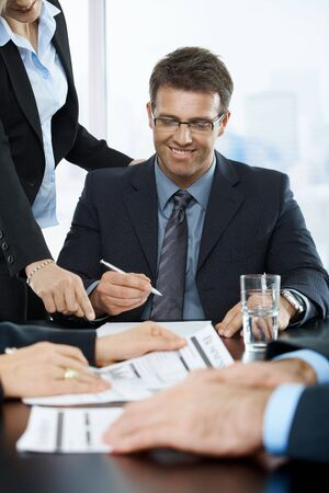 Smiling executive signing contract in office, assistant pointing at paper, photo