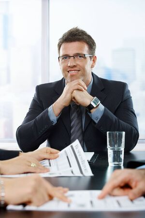 Confident businessman  at meeting, smiling at camera with hands folded. photo
