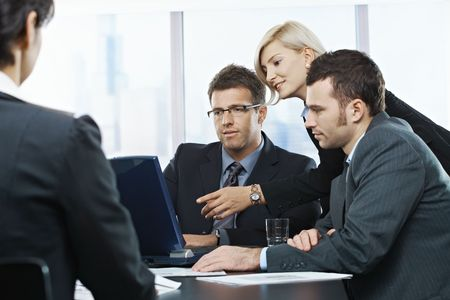 Businessmen looking at laptop, businesswoman pointing at screen in office, at meeting table, photo