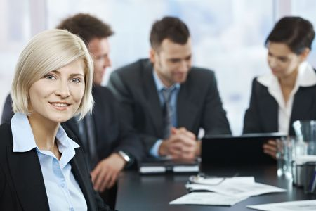 Portrait of mid-adult businesswoman smiling at camera with colleagues at meeting in background, photo