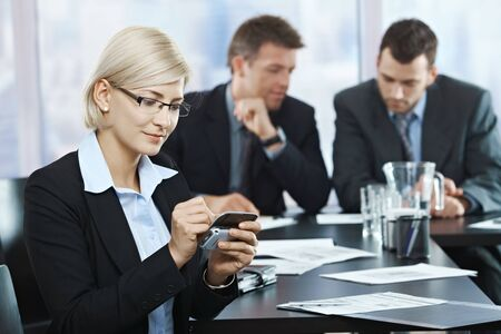 Smiling businesswoman using smartphone at office meeting with colleagues in background. photo