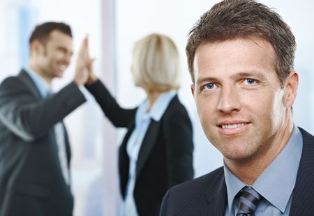 Successful businessman smiling at camera, with coworkers clapping hands together in background. photo