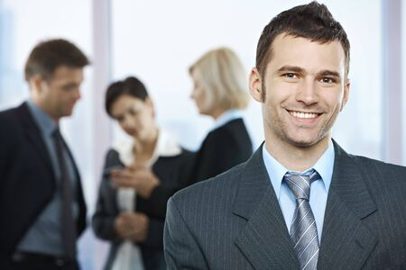 Portrait of happy businessman with coworkers talking in the background. photo