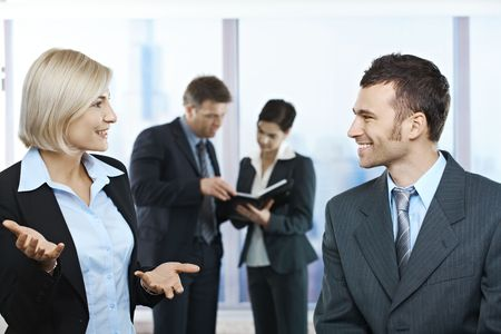 Standing businesspeople talking in office smiling at each other, coworkers looking at documents in background. photo