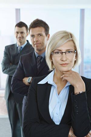 Portrait de professionnels confiants debout dans une ligne avec armes plié dans office.  Banque d'images