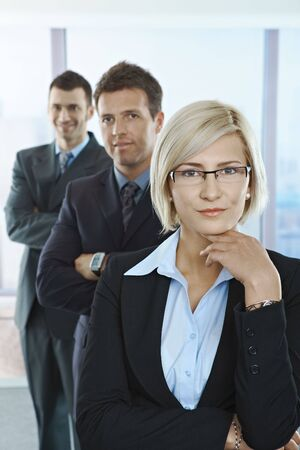 Portrait of confident professionals standing in a row with arms folded in office. photo
