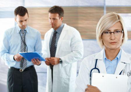 doctora: Trabajadores sanitarios en el corredor de hospital femenino m�dico mirando al frente de c�mara.
