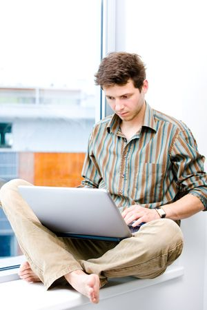 Young casual office worker sitting at office window working on laptop computer. Stock Photo - 6549191