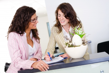 Happy businesswomen working together in team at office reception, looking at documents, talking, smiling. photo