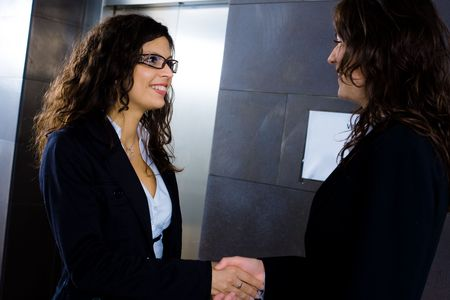 hand wear: Smiling businesswomen shaking hands at office lobby in front of elevator. Stock Photo