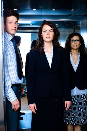 Young business people arriving to office, using elevator. photo