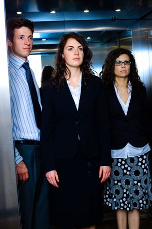 Young business people standing in elevator. Stock Photo - 6550693