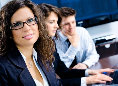 Small team of young happy businesspeople working together at meeting room at office. Huge plasma TV screen in background. Stock Photo - 6550647