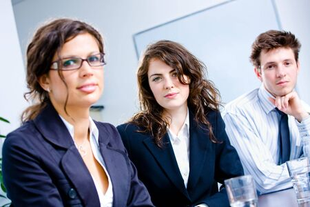 Businesspeople sitting in a row on a meeting at office. photo