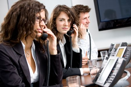 Young customer service operator team working at office, holding phone, calling, giving helpdesk support. Stock Photo - 6567249
