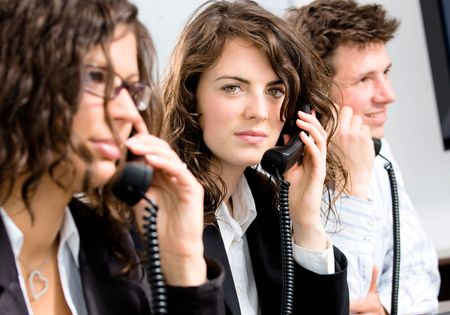 Young customer service operator team working at office, holding phone, calling, giving helpdesk support. photo