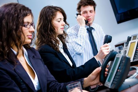 Young customer service operator team working at office, holding phone, calling, giving helpdesk support. Stock Photo - 6544851