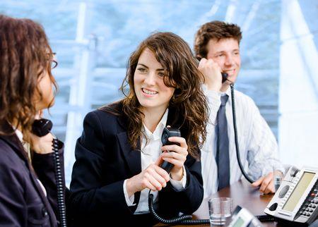 Happy team of customer service operators calling on phone. photo