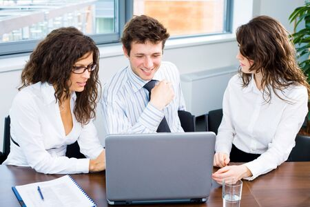 Happy young business people having meeting at office, talking over laptop computer, smiling. Stock Photo - 6550717