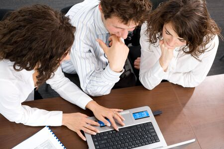 color consultant: Young businesspeople sitting by table at office, working together on laptop computer. High-angle view. Stock Photo