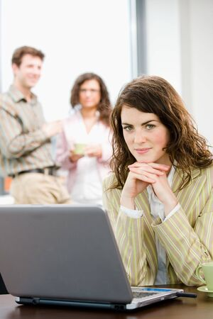 young office workers: Team of young successful office workers talking and drinking coffee at meeting room, businesswoman working on laptop computer in front.  Stock Photo