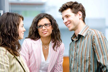 talking businessman: Feliz j�venes empresarios hablando en frente de la ventana de la Oficina, sonriente, amistad.
