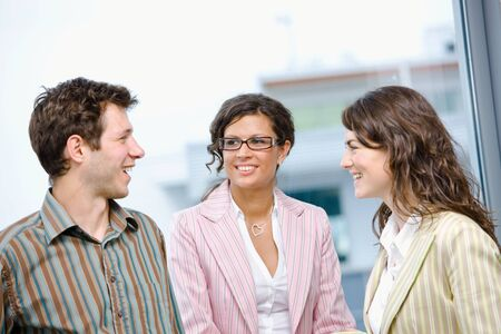 Happy young business people talking in front of office window, smiling, friendship. photo