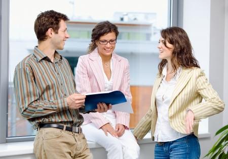 amigas conversando: Empresarios j�venes felices tener la reuni�n en la Oficina y la lectura de documentos, sonriendo.