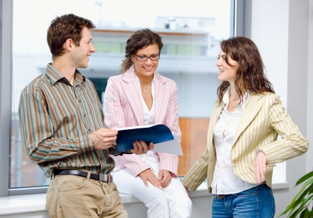 Happy young businesspeople having meeting at office and reading documents, smiling. photo